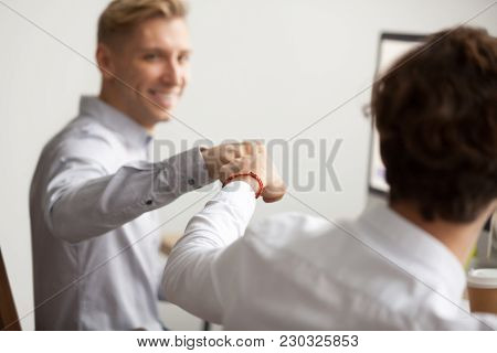 Smiling Male Colleagues Fist Bumping At Workplace, Happy Friends Greeting, Partners Sharing Success,