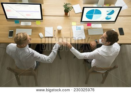 Smiling Colleagues Fist Bumping Sitting At Workplace, Young Motivated Coworkers Greeting Working Tog