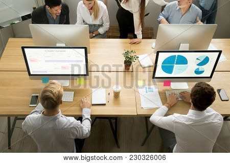 Male Employees Using Computers For Planning And Data Analysis Sharing Coworking Desk Working With Mu