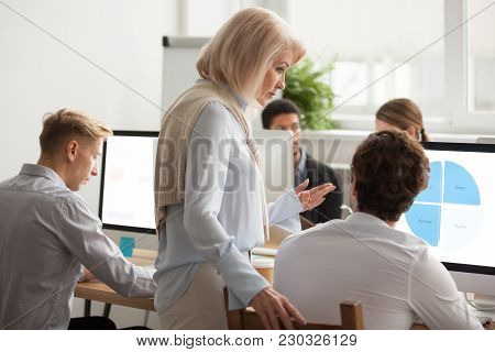 Senior Female Executive Boss Supervising Computer Work Of Young Employee, Serious Aged Woman Mentor