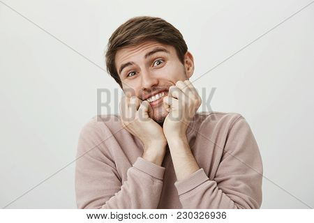 Portrait Of Pleased Good-looking Funny Man Holding Clenched Fists In Mouth, Smiling And Tilting Head