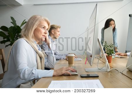 Focused Senior Businesswoman Employee Working On Desktop Sitting At Coworking Office Desk, Serious O
