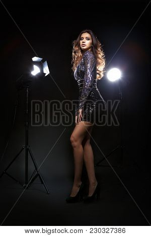 Beautiful Female Model In Blue Evening Dress Posing At Photo Studio In Light Flashes