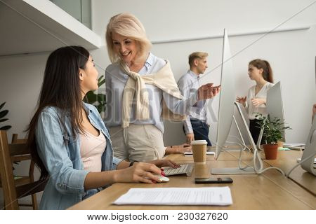 Smiling Friendly Senior Female Executive Talking To Asian Employee Working On Pc, Happy Aged Leader