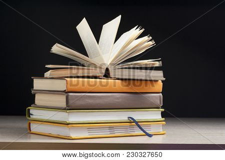 Stack Of Books On Wooden Table On Black Background. Back To School. Education Background.