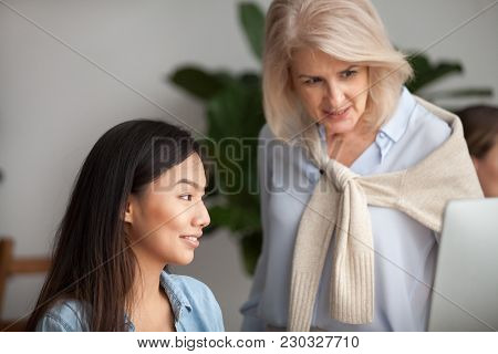 Smiling Aged Leader Checking Computer Online Work Of Asian Employee Looking At Pc Screen, Friendly S