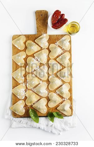 Ravioli In A Heart Shape. Cutting Board With A Group Of Raw Freshly Homemade Ravioli . Ready To Be C