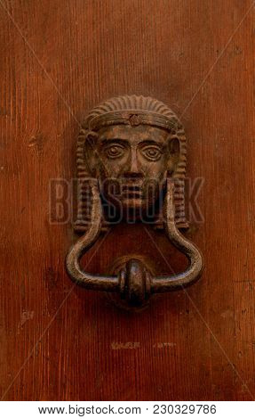 Antique Decorative Brass Door Knocker In The Shape Of Egyptian Pharaoh On Old Wooden Door, Italy. An