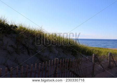 A Beach Fence In Front Of Sand Dunes On Cape Cod Hiding The Sun