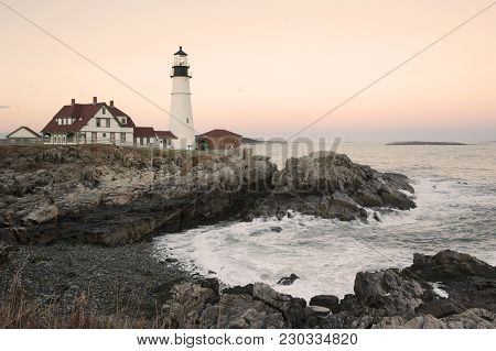Sun Setting By Portland Head Lighthouse In Maine In Autumn.