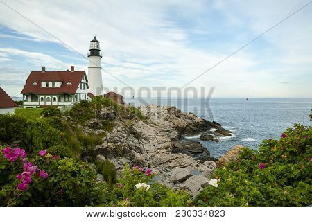 Portland Head Lighthouse Surrounded By Rocks, Ocean, And Beach Roses On A Warm Summer Day In Maine.