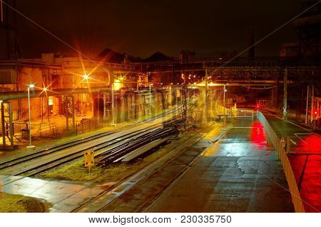Industrial Rail Yard Shunting Station At Night With Many Lights And Wagons On A Siding In An Industr