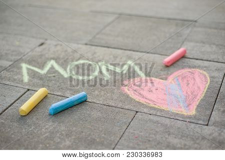 Happy Mother's Day. Child Draws For Her Mother A Picture Surprise Of Crayons On The Asphalt. Love Mo