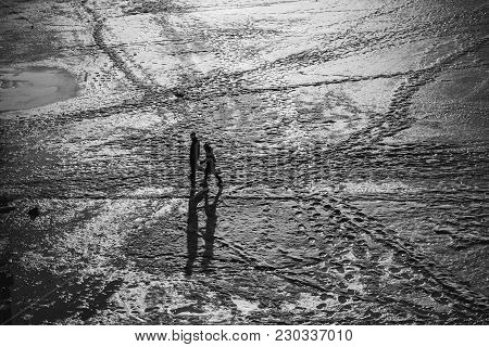 Man Walking In A Desert Towards A City. Black And White Picture. High Contrast. View From Above