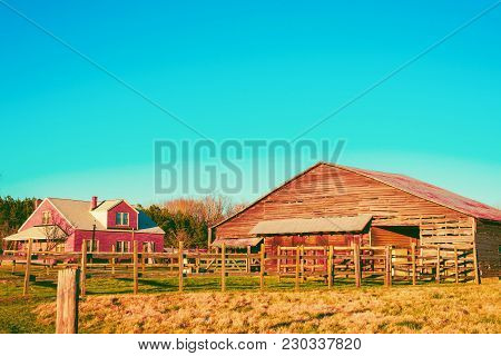 A Landscape Of A Farmhouse Near An Old Wooden Barn And Corral In A Candy Color.