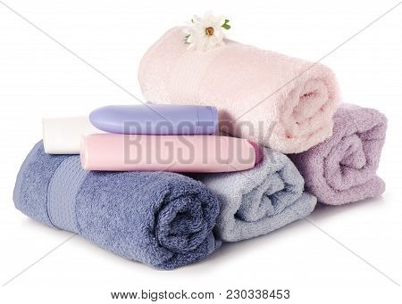 A Stack Set Towels Plastic Bottle With Cosmetic  Cream Lotion Gel For Body Flower On White Backgroun
