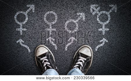 A Person Standing On Asphalt Road With Gender Symbols Of Male, Female, Bigender And Transgender.  Co
