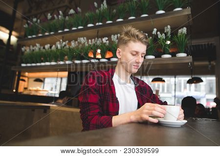 Stylish Young Man In A Red Trash Sits In A Cafe With A Cup Of Coffee. Breakfast A Look At A Drink At