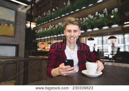 A Smiling Student Sitting In A Cafe With A Cup Of Coffee And A Smartphone In His Hands And Looking I