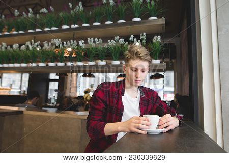 A Thoughtful Young Man Sits In A Cafe With A Donut Of Coffee. Look At The Drink In A Cozy Cafe.