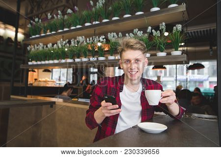 A Positive Young Man Holds A Cup Of Coffee In His Hands And Looks At The Camera. A Student Drinks Co