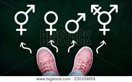 A Person Standing On Chalkboard With Gender Symbols Of Male, Female, Bigender And Transgender.  Conc