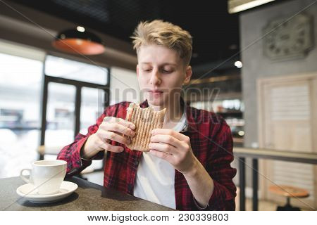 Young Man Dining Panini Sandwich In Restaurant. A Student With Appetite Looking At A Sandwich In His