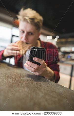 A Funny Young Man Uses A Smartphone And Eats In A Cafe. Focus On Your Phone.