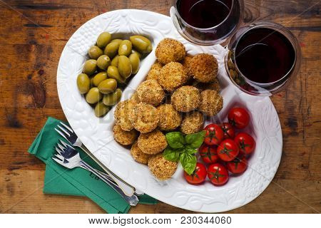 Healthy Italian Appetizer With Risotto Balls Arancini , Green Olives , Tomato And Red Wine
