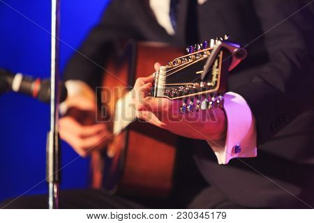 Singer With Guitar Playing Pop Or Classic Music On A Colorful Fancy Background. Singer In Elegant Co
