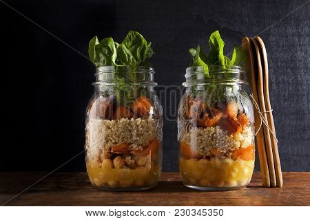 Mason Jars With Hot Salad: Chickpeas, Arrots, Quinoa, Roasted Pumpkin, And Spinach. Healthy Lunch