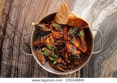 Mussels cooked with hot Italian arrabiata sauce and served in metal pot