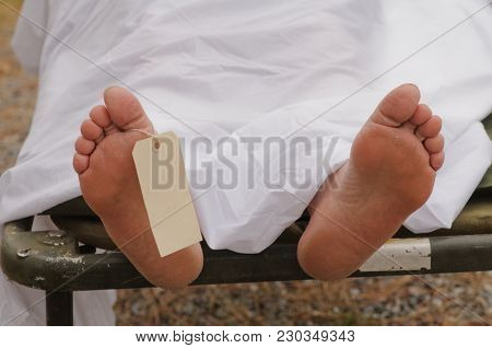 Dead mans feet with toe tag
