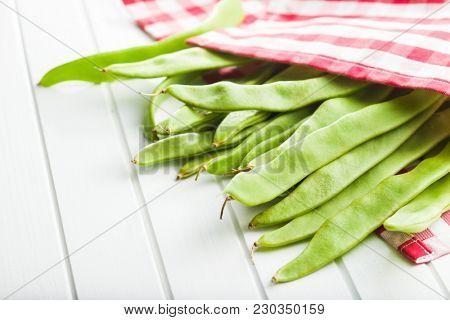 Green string beans pods on white table.