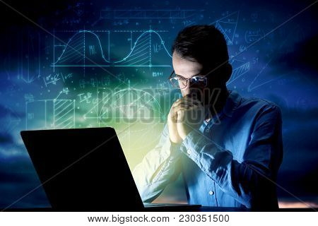 Young handsome businessman working late at night in the office with blue mathematic charts in the background