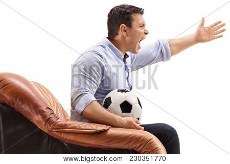 Angry young man with a football sitting in an armchair and yelling isolated on white background