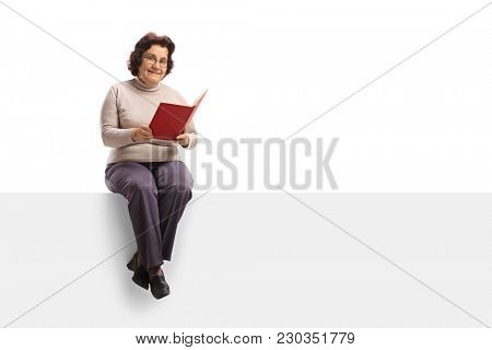 Elderly woman with a book sitting on a panel isolated on white background