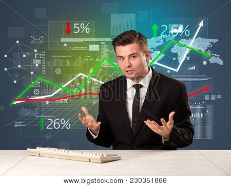 Young handsome businessman sitting at a desk with stocks and progress charts behind him
