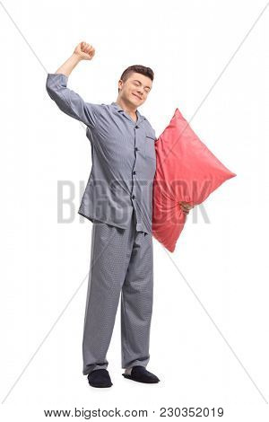 Full length portrait of a teenage boy in pajamas holding a pillow and stretching himself isolated on white background