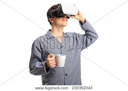 Teenager in pajamas using a VR headset and holding a cup isolated on white background