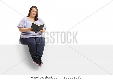 Overweight woman sitting on a panel and reading a book isolated on white background
