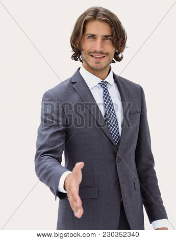 Smiling friendly businessman offers a handshake