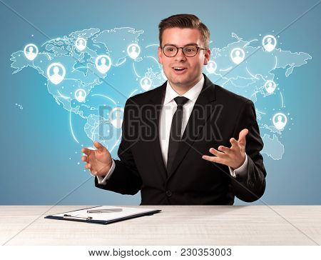 Young handsome businessman sitting at a desk with a blue world map behind him
