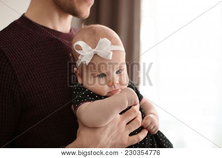 Young father with his cute little baby at home