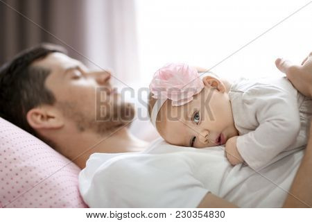 Young father and his baby on bed at home