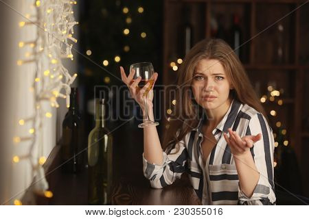 Young woman with glass of wine in bar. Alcoholism problem