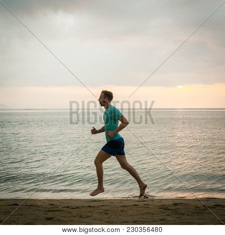 Full length side view of an athletic young man running on the beach during cardio workout session in summer vacation in Indonesia