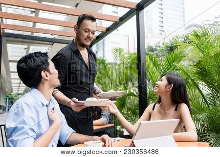 Cheerful waiter bringing two plates of food to the table of a young couple in a modern location downtown in Asia