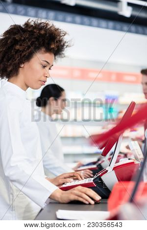 Side-view of a cheerful pharmacist holding two packs of prescribed medicine, while giving advices and useful information to a young male customer in a modern drugstore