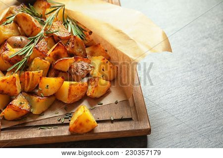 Wooden board with tasty potato wedges on table